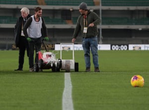 Staff work on the pitch in Verona.