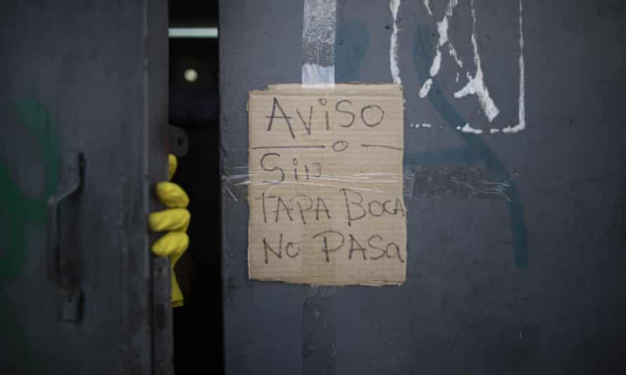 A piece of cardboard is taped to a supermarket door with a handwritten message saying 'Notice: without a face mask, no entry' in Caracas, Venezuela.