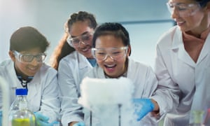 High school students conducting scientific experimentCurious, smiling students watching chemical reaction, conducting scientific experiment in laboratory classroom