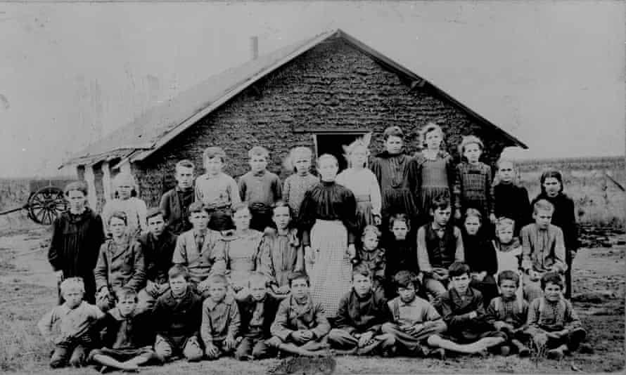 1895 photograph of a teacher, students, and schoolhouse.