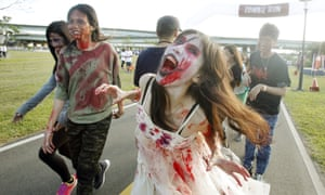 Runners dressed as zombies race during the Zombie Run Taiwan.