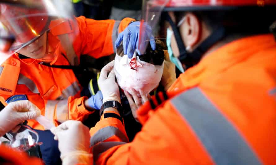 An injured young woman receives medical assistance after being hit in one eye during a demonstration in Hong Kong.