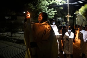 A priest walks towards the church with the paschal candle during the Easter vigil