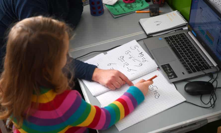 Young girl in colourful jumper doing maths in front of computer