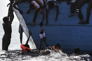 A child is pulled out of the water as people wait to be rescued by members of Proactiva Open Arms NGO