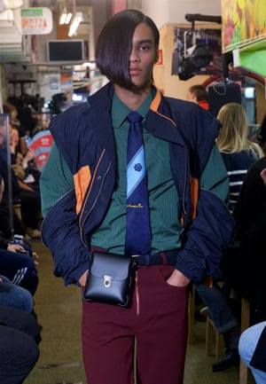 A male model on the catwalk in a green shirt, blue tie, blue and orange bomber jacket and burgundy trousers
