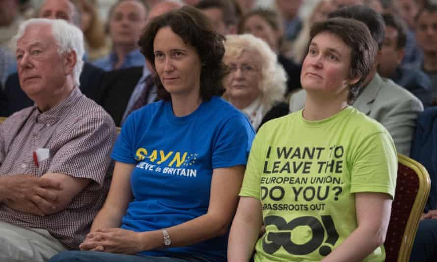 Two women listen to Nigel Farage speak at a rally