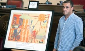 Kamaran Ahmad Ali, brother of Kamil Ahmad, with the memorial image