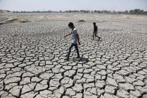 Boys walk through the dried-up Chandola lake on their way to play cricket in Ahmadabad