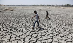 Two boys walk through a dried up Chandola Lake in Ahmadabad, India, May 2016