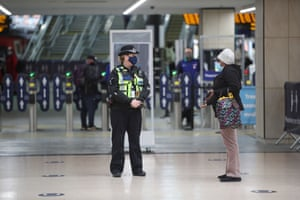 A police officer speaks to a passenger to see where they are going at Leeds train station