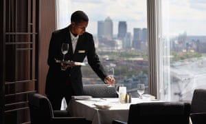 A waiter lays a table ahead of a reception at a hotel