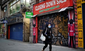 A pedestrian wearing a face mask as a precautionary measure against Covid-19, walks past a shuttered souvenir shop on Oxford Street, central London on 15 January