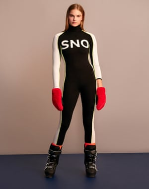 A model wearing a black with white sleeves all-in-one ski suit, red gloves and black ski boots