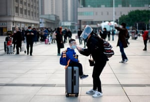 A woman wearing a face mask adjusts her child's mask as they arrive at Hankou Railway Station in Wuhan to take one of the first trains leaving the city