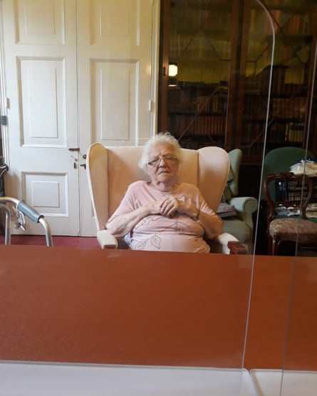 Eve behind a perspex screen in her care home in a photo taken by her daughter.