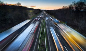 Light trails of fast-moving cars on a busy motorway at dusk