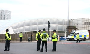 Police officers stand at the Miller Street and Corporation Street crossroads in front of the Manchester Arena.