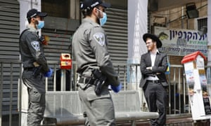 Israeli border police officers speak to an Ultra orthodox man as the Israeli government moves forward with measures to help stop the spread of the coronavirus in the orthodox city of Bnei Brak, a Tel Aviv suburb, Israel. ‏