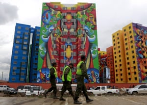 Police officers pass a housing programme in El Alto.