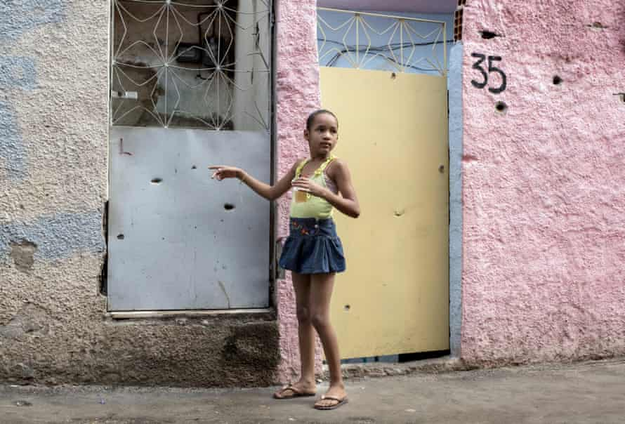A young girl points to bullet holes in the front of her house in the Complexo do Alemão.