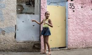 Uma menina indica buracos da bala na sua casa em Complexo do Alemão, Rio de Janeiro.
