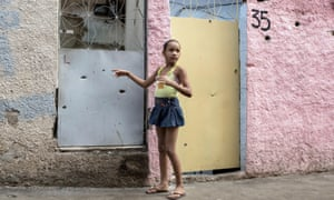 A young girl points to bullet holes in the front of her house in the favela Complexo do Alemao in Rio de Janeiro, Brazil.