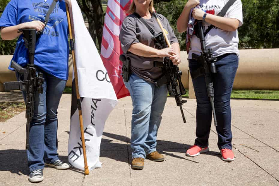 Demonstrators open-carry rifles while holding flags during a pro-gun rally on the sidelines of the National Rifle Association annual meeting in Dallas, Texas, on 5 May 2018.