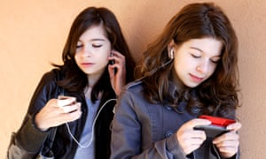 Two teenage girls listening to music on an MP3 player