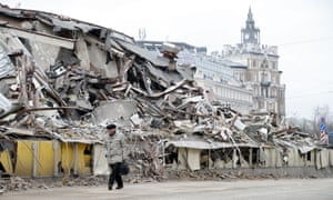 Muscovites pass by a demolished shopping facility in central Moscow
