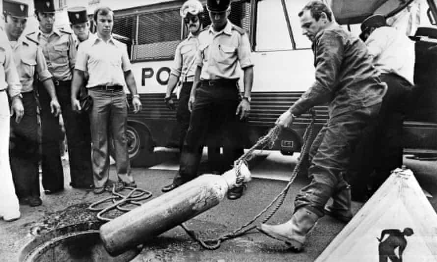 Police watch as an acetylene tank is pulled from the sewers of Nice days after the bank was robbed by a gang.