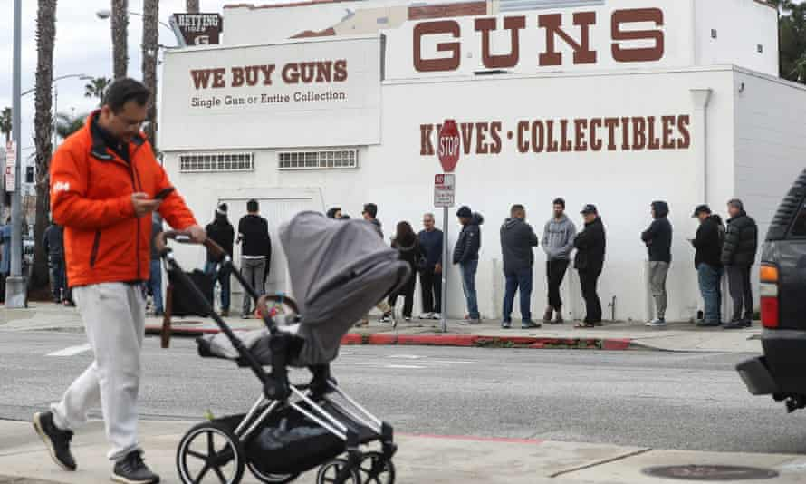 People stand in line outside the Martin B Retting, Inc guns store in Culver City, California. The spread of Coronavirus has prompted some Americans to line up for supplies in a variety of stores.