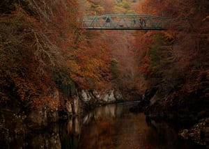 People walk on the bridge over the river Garry in Pitlochry.