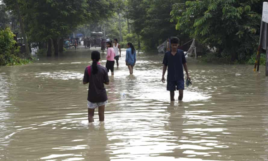 People cross a flooded road in Kamrup district, Assam, India.