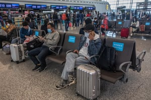 Passengers wearing protective face masks wait at the airport