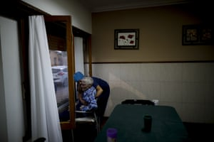 Nurse Rocio Lescano helps Victor Tripiana in his chair in front of a window where he can see his visiting family at the Reminiscencias residential home for the elderly in Tandil.