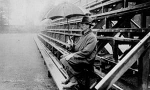 A spectator shelters from the rain as he hopes for play to resume at a cricket match in 1924