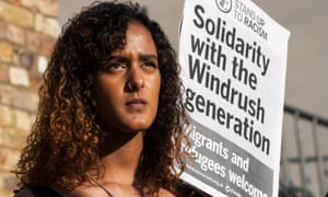 Woman with poster saying 'solidarity with the Windrush generation'
