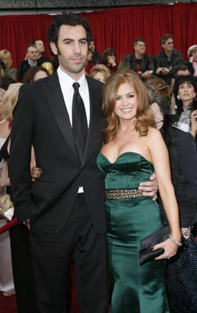 Sacha Baron Cohen and his girlfriend Isla Fisher present a rather solemn face to the baying wolf-fans. Baron Cohen's Borat is nominated in the best adapted screenplay category. Adapted from what, exactly? Viz?