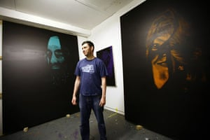 Artist Leigh Clarke stands in front of his painting at his studio in Hackney