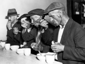 Men eating bread and soup in a breadline during the Great Depression