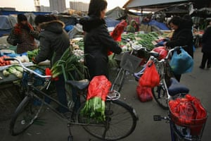 Chinese women buy vegetables with plastic bags at a food market. The Chinese Government has announced a nationwide ban on stores distributing free plastic bags from June 1