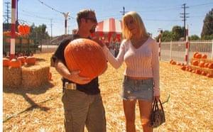 A woman touches her friend's giant pumpkin