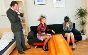 A man watches two women grieve after a funeral