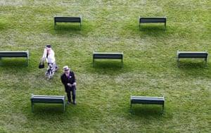Racegoers walk past seats in the Royal enclosure