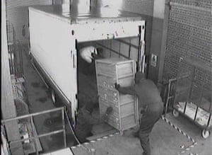 1.39am The money stored in cages is loaded onto a lorry