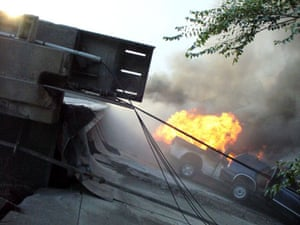 Vehicles burn in the wreckage of the bridge