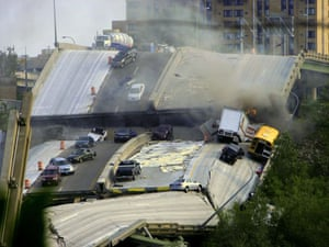 Vehicles are scattered along the broken remains of the Interstate 35W bridge