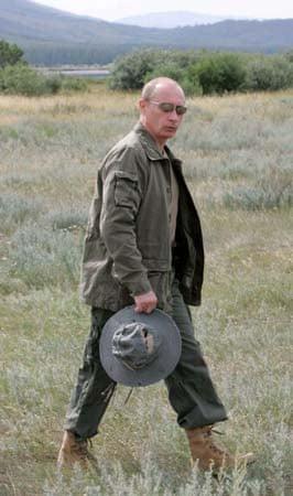Vladimir Putin walks in the grass before fishing