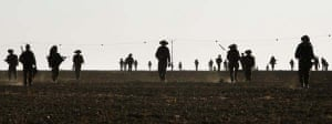 Infantry soldiers walk out of Gaza